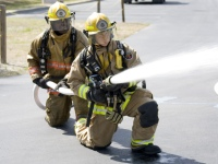 Two firefighters use firehose