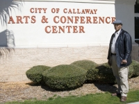 Director in front of Arts and Conference Center sign
